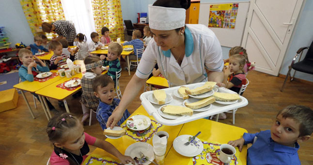 ROSTOV-ON-DON, RUSSIA. DECEMBER 9, 2015. A dinner lady hands out cheese sandwiches to children as they are having breakfast, at Kindergarten ¹ 1. Valery Matytsin/TASS